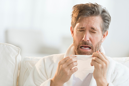 Man Sneezing Into Tissue